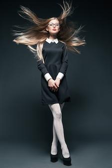 Portret blond młoda piękna pozowanie kobieta nosi okulary i czarną sukienkę z białym kołnierzykiem. jej długie włosy powiewały na wietrze i skrzyżowały nogi.
