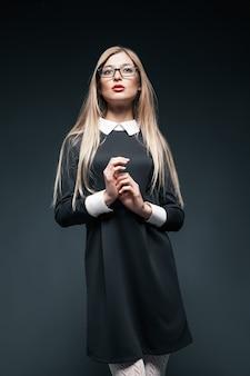 Portret blond młoda piękna pozowanie kobieta nosi okulary i czarną sukienkę z białym kołnierzykiem. jej ręce razem.