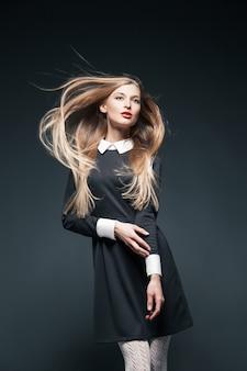 Portret blond modelka pozuje z włosami powiewającymi na wietrze i dotykając jej ramienia.