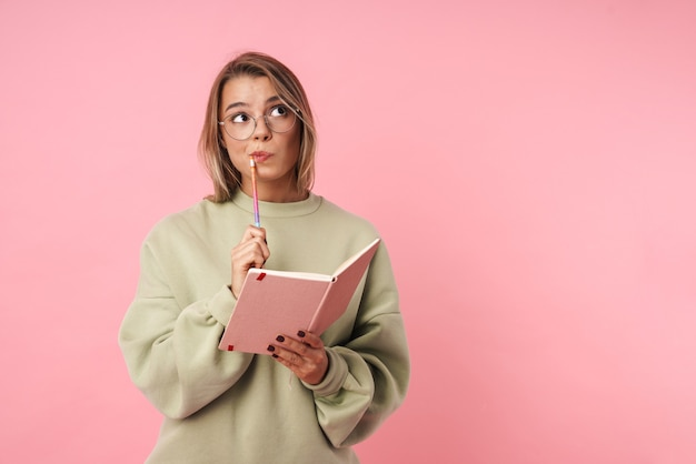 Portret blond myśląca kobieta w okularach trzymająca pamiętnik i patrząca w górę