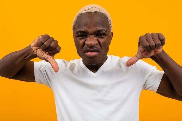 Portret blond niezadowolony charyzmatyczny afrykański mężczyzna w białej koszulce, trzymając palce w dół na żółtym tle studio