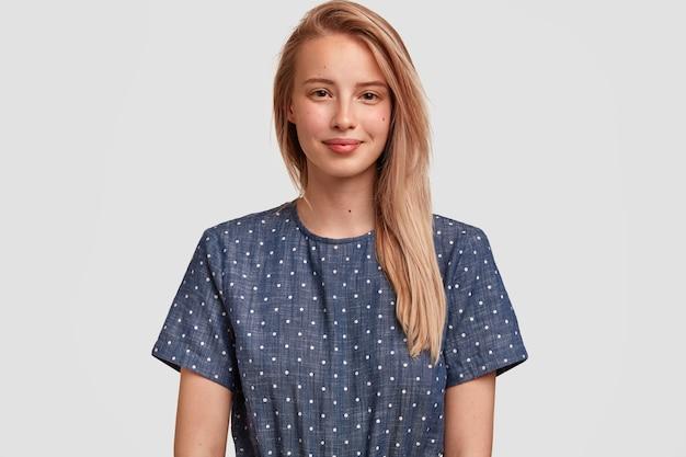 Portret blond optymistycznej młodej modelki w pasie ma zadowolony wyraz twarzy, stoi samotnie, raduje się z długich weekendów, nosi elegancką koszulkę w kropki, odizolowaną na białej ścianie