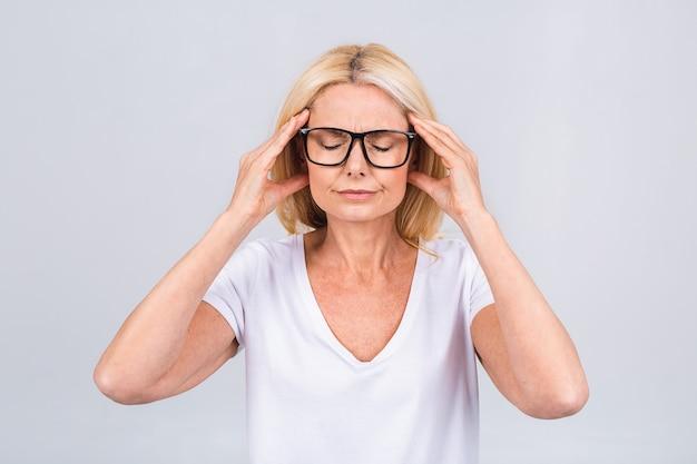 Portret blond podkreślił zmęczoną, zmęczoną, dojrzałą starszą kobietę na białym tle na szarym tle koloru białego.