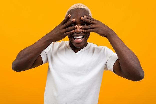 Portret blond przystojny afrykański murzyn zamykający oczy rękami w białej koszulce na żółtym pracownianym tle