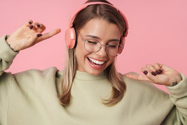 Portret blond szczęśliwa kobieta w okularach za pomocą słuchawek i taniec na białym tle nad różową ścianą