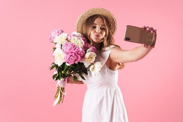 Portret blond szczęśliwa kobieta w słomkowym kapeluszu robi pocałunek i robi selfie portret na telefonie komórkowym z kwiatami izolowanymi na różowej ścianie