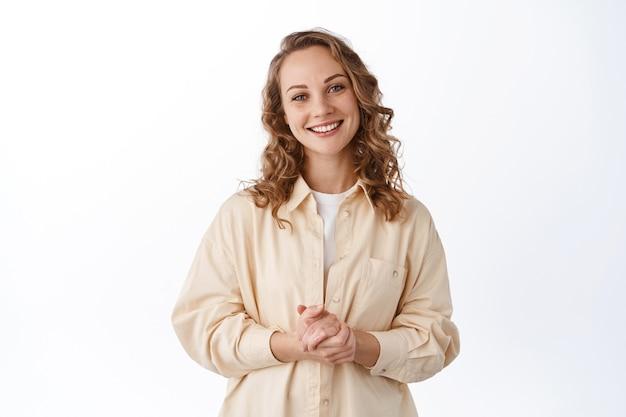 Portret blond uśmiechniętej kobiety trzymającej ręce zaciśnięte razem, gotowej do pomocy, wyglądającej przyjaźnie i uroczo, do usług, stojącej nad białą ścianą