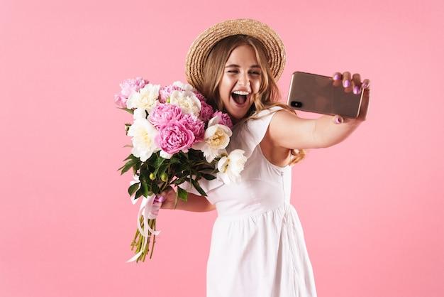 Portret blond zachwycona kobieta w słomkowym kapeluszu robi selfie portret na telefonie komórkowym i trzyma kwiaty izolowane nad różową ścianą