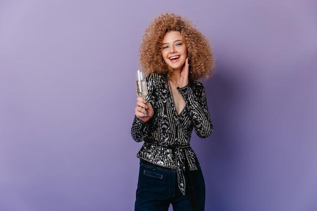 Portret blondynka kręcone dziewczyna w błyszczącej czarnej bluzce, śmiejąc się i trzymając kieliszek białego wina na fioletowej przestrzeni.