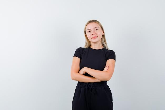 Portret blondynka stoi ze skrzyżowanymi rękami w czarnej sukience i patrząc dumny widok z przodu