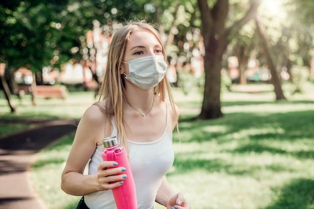 Portret blondynka ubrana w ochronną maskę medyczną biegnącą przez słoneczny park