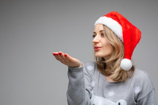 Portret blondynka w szarym swetrze i czerwonym czapce mikołaja wysyłając pocałunek ręką