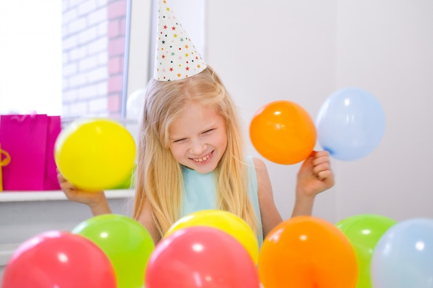 Portret blondynki caucasian dziewczyna ono uśmiecha się przy kamery przyjęciem urodzinowym. świąteczne kolorowe tło z balonów. zdjęcie pionowe