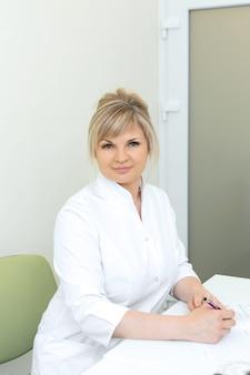 Portret blondynki doktorska kobieta w białym żakieta obsiadaniu przy stołem w medycznym biurze
