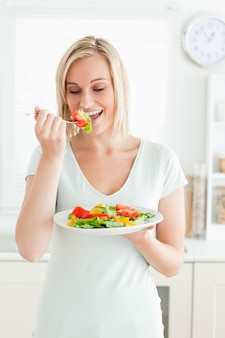 Portret blondynki kobieta cieszy się mieszanej sałatki