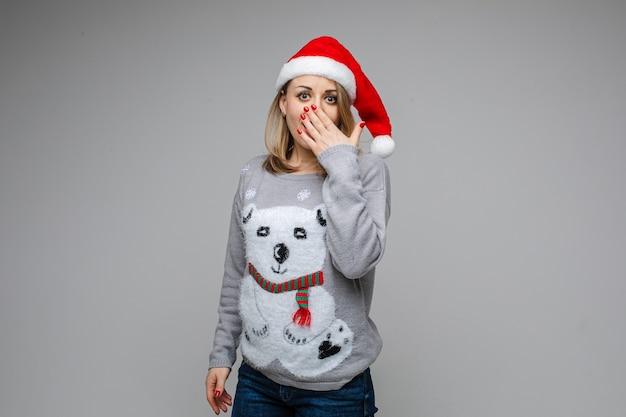 Portret blondynki kobieta w czapce mikołaja i świątecznym swetrze z niedźwiedziem obejmującym usta ręką ze zdumienia
