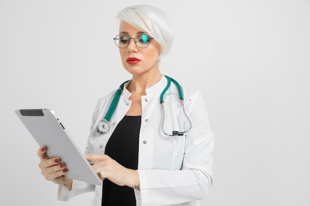 Portret blondynki kobieta w lekarkach kostiumowych z pastylką w ona ręki odizolowywać dalej