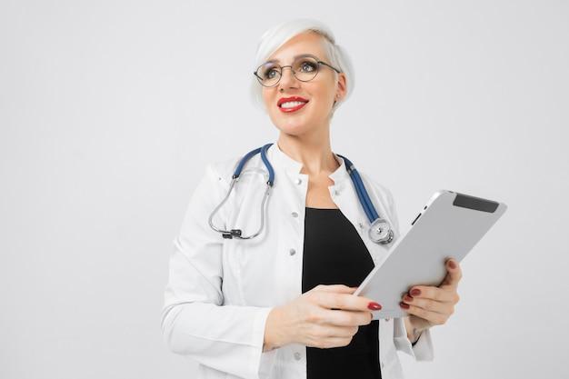 Portret blondynki kobieta w lekarkach kostiumowych z pastylką w ona ręki odizolowywać