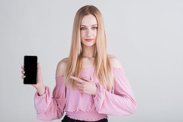 Portret blondynki, która pokazuje ekran smartfona i wskazuje na niego palcem