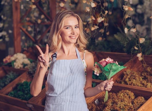 Portret blondynki kwiaciarki młody żeński mienie w ręce robi zwycięstwo gestowi