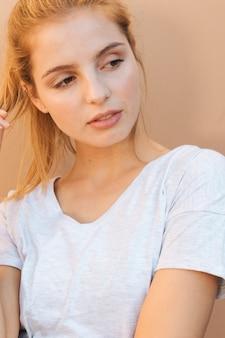 Portret blondynki młoda kobieta patrzeje daleko od przeciw beżowemu tłu