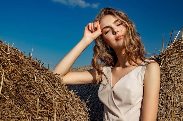 Portret blondynki młodej dziewczyny model, który stoi i pozuje w słonecznym dniu