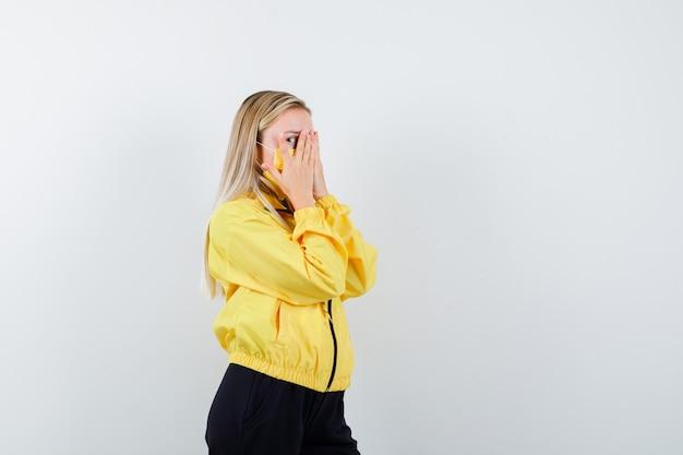Portret blondynki patrząc przez palce w dresie, masce i patrząc przestraszony widok z przodu
