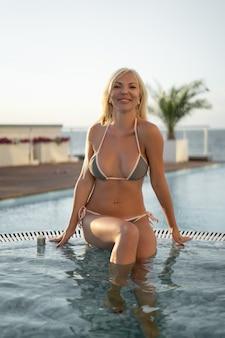 Portret blondynki siedzącej na brzegu basenu w hotelu w letnim kurorcie. odpoczynek i odprężenie