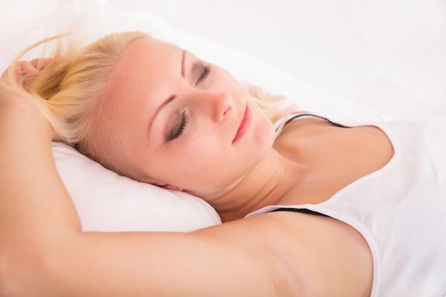 Portret blondynki śpi w łóżku.