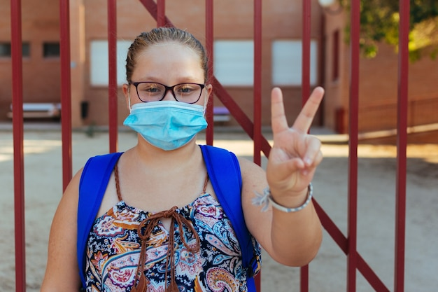 Portret blondynki z niebieskim plecakiem i maską na twarz. symbol zwycięstwa. powrót do szkoły.
