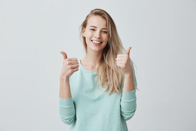Portret blondynki żeńska kobieta z szerokim uśmiechem i aprobatami gestykuluje