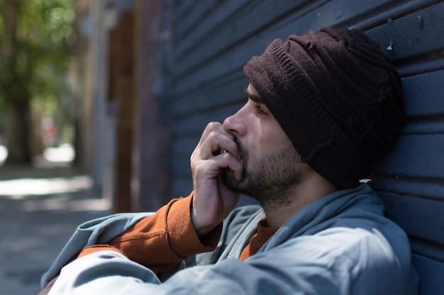 Portret bokiem bezdomnego jest zdenerwowany