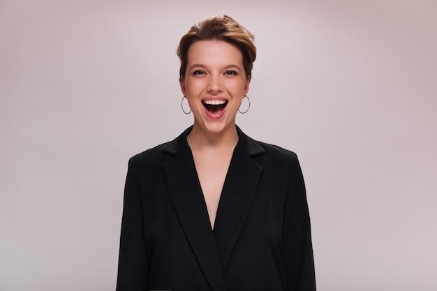 Portret brązowooki dama w ciemnej kurtce na na białym tle. atrakcyjna krótkowłosa kobieta w czarnym garniturze śmieje się i patrzy w kamerę na białym tle