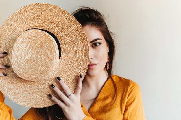 Portret brązowookiej dziewczyny zakrywającej twarz słomianym kapeluszem. piękna pani w jasnym stroju