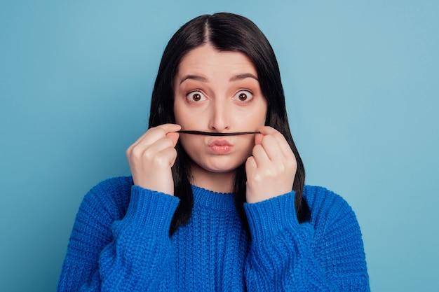 Portret brązowowłosej wspaniałej miłej młodej damy skrzywiącej się ze sztucznymi wąsami na niebieskim tle