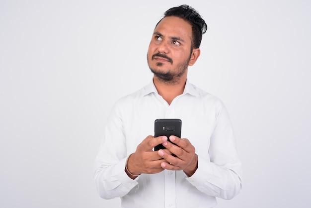 Portret brodatego indyjskiego biznesmena za pomocą telefonu i myślenia