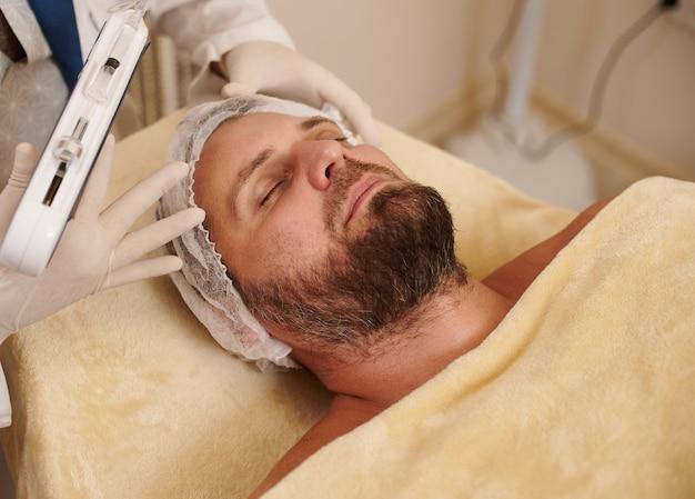 Portret brodatego mężczyzny leżącego na stole do masażu w salonie kosmetycznym, gotowy do zabiegu mezoterapii
