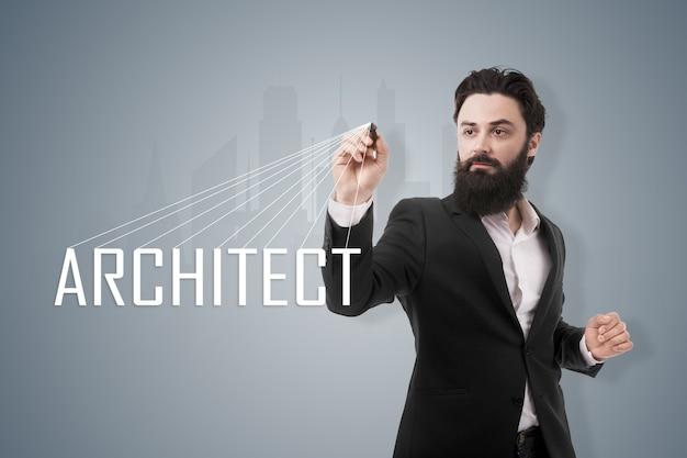 Portret brodatego mężczyzny piszącego rysikiem architekta napisów, nad ilustracją nowoczesnej panoramy miasta