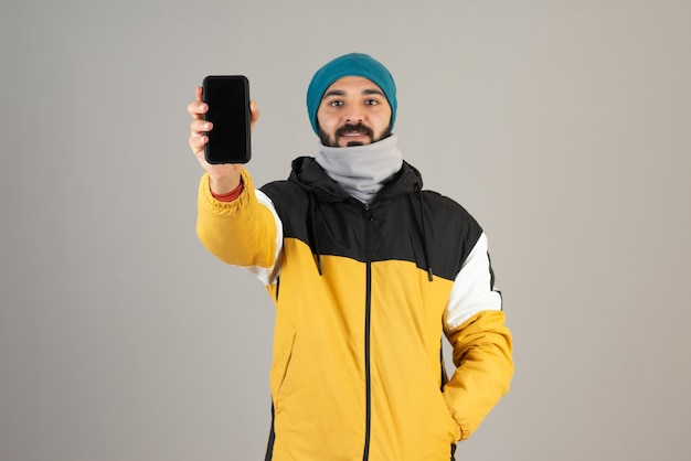 Portret brodatego mężczyzny w ciepłych ubraniach pokazujących jego telefon komórkowy