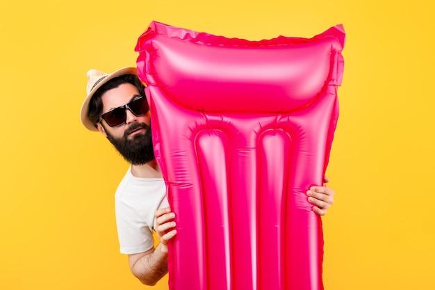 Portret brodatego mężczyzny w okularach przeciwsłonecznych i kapeluszu z różowym nadmuchiwanym materacem do pływania