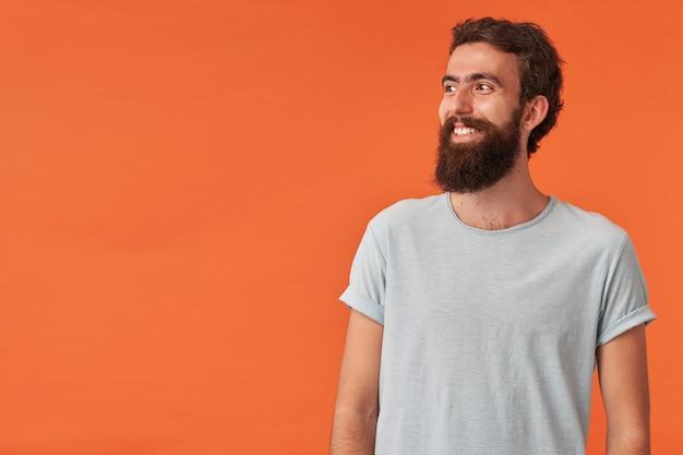Portret brodatego młodzieńca o brązowych oczach w zwykłych ubraniach biała koszulka patrzy na bok i w górę emocje szczęśliwy zadowolony uśmiech na bok