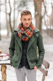 Portret brodatego pana młodego w stylowym garniturze z szelkami i muszką zimą w ośrodku narciarskim