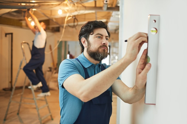 Portret brodatego pracownika budowlanego pomiaru poziomu ściany podczas remontu domu, miejsce na kopię