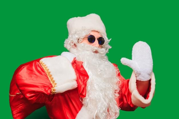 Portret brodatego starca w stroju świętego mikołaja niosącego duży worek z prezentami świątecznymi w pasie. pojedynczo na zielonej ścianie