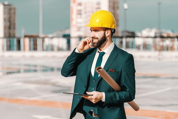 Portret brodaty architekt opowiada na telefonie, trzyma projekt i pastylkę w formalnej odzieży podczas gdy stojący na budowie.