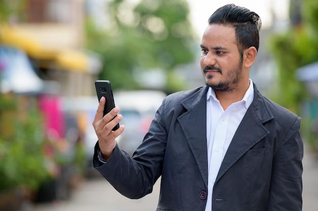 Portret brodaty biznesmen indyjski na sobie garnitur na ulicy na zewnątrz