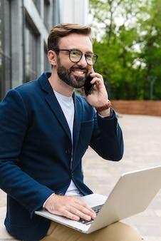 Portret brodaty biznesmen w okularach rozmawia przez telefon komórkowy i za pomocą laptopa siedząc na zewnątrz w pobliżu budynku