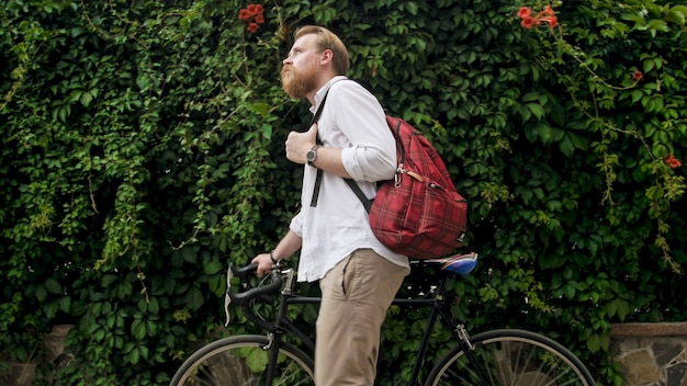 Portret brodaty hipster mężczyzny chodzenie z rocznika roweru w parku.