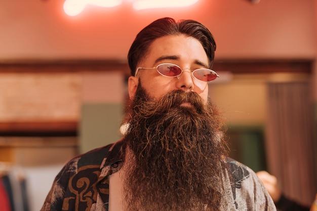 Portret brodaty mężczyzna jest ubranym okulary przeciwsłonecznych w sklepie