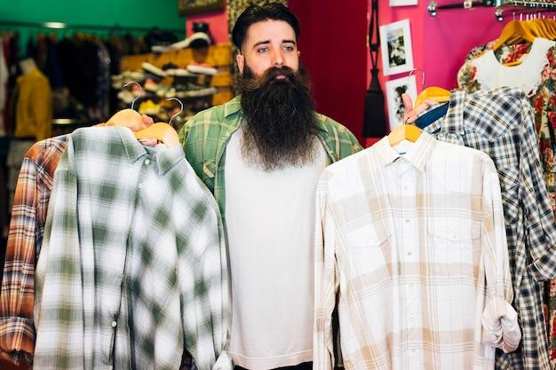 Portret brodaty mężczyzna trzyma koszula w wieszaku